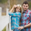 Portrait of happy young couple wearing shirts having fun outdoors near fence in park — Stock Photo #41086831