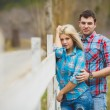 Portrait of happy young couple wearing shirts having fun outdoors near fence in park — Stock Photo #41086863
