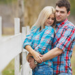 Portrait of happy young couple wearing shirts having fun outdoors near fence in park — Stock Photo #41087019
