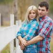 Portrait of happy young couple wearing shirts having fun outdoors near fence in park — Stock Photo #41087049