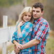 Portrait of happy young couple wearing shirts having fun outdoors near fence in park — Stock Photo #41087127