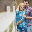 Portrait of happy young couple wearing shirts having fun outdoors near fence in park — Stock Photo #41088603