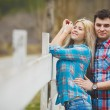 Portrait of happy young couple wearing shirts having fun outdoors near fence in park — Stock Photo