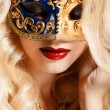 Portrait of a beautiful young blond woman with theatrical mask on his face on a dark background — Foto Stock