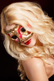 Portrait of a beautiful young blond woman with theatrical mask on his face on a dark background — Stock Photo