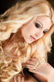 Portrait of an attractive blond woman with long curly hair, isolated on black studio shot — Stock Photo