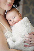 Portrait of happy young attractive mother with her baby ion hands n home interior — Stock Photo
