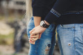 Young couple in love walking in autumn park holding hands — Stock Photo