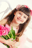 Adorable little girl with bouquet of tulips — Stockfoto