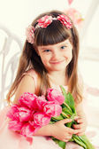 Portrait of a beautiful little girl with flowers — Stock Photo