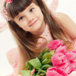 Close up portrait of little adorable girl holding pink tulips in her hands. — Stock Photo