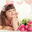 Close up portrait of little adorable girl holding pink tulips in her hands. — Stock Photo #42525163