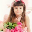 Close up portrait of little adorable girl holding pink tulips in her hands. — Stock Photo #42525177