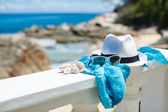 Hat and sunglasses on background of ocean beach — Stock Photo