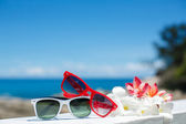 Two pairs of sunglasses on background of ocean — Stock Photo