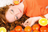 Portrait of attractive caucasian smiling woman isolated on white studio shot with oranges — Stock Photo