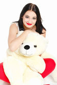 Beautiful young brunette woman holding a teddy bear — Stock Photo