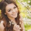 Portrait of young brunette in the spring blooming garden — Stock Photo #42946191