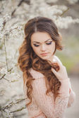 Portrait of young brunette in the spring blooming garden — Stock Photo