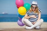 Pregnant woman in sunglasses and a white hat with balloons — Stock Photo