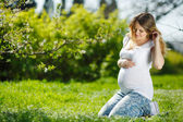 Portrait Healthy pregnant woman sitting on green grass — Stock Photo