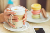 A hot Cup of coffee latte with colorful sculpture cookies — Stock Photo