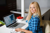 Smiling young woman sitting with a laptop — Stock Photo