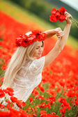 Beautiful young blonde woman in red bright poppy field. — Stock Photo