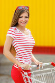 Beautiful girl with a basket in a large supermarket — Stock Photo