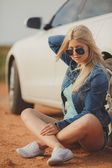 Portrait of a young pretty blonde with luxury car — Stock Photo