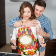 Young couple making a salad together in the kitchen — Stock Photo