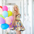 Beautiful smiling blond girl with colorful balloons — Stock Photo #47188919