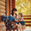 MOM with kids, sitting near a wooden house — Stock Photo