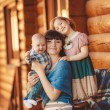 MOM with kids, sitting near a wooden house — Stock Photo #47524881