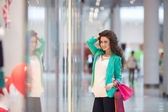 Beautiful young woman with shopping bags and gifts. — ストック写真
