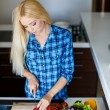 A young woman prepares fresh vegetable salad — Stock Photo #47780455