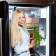 Beautiful young woman near the fridge with healthy food. — Stock Photo