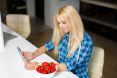 Happy young housewife with tablet pc eating fruits — Stock Photo