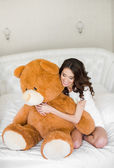 Pretty girl lying on the bed with a teddy bear — Stock Photo