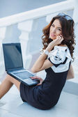 Young woman sitting with a laptop on a summer day — Stock Photo