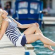 Adorable blonde woman wearing sea shorts and sexy sailor T-shirt sitting on yachts background and the sea — Stock Photo #48683139
