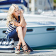Adorable blonde woman wearing sea shorts and sexy sailor T-shirt sitting on yachts background and the sea — Stock Photo #48683275