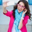 Happy young girl making funny face while taking pictures of herself through cellphone, over white background — Stock Photo #48684013