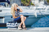 Adorable blonde woman wearing sea shorts and sexy sailor T-shirt sitting on yachts background and the sea — Foto de Stock