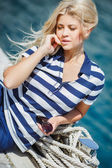 Adorable blonde woman wearing sea shorts and sexy sailor T-shirt sitting on yachts background and the sea — Stock Photo