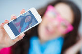 Happy young girl making funny face while taking pictures of herself through cellphone, over white background — Stock Photo