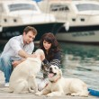Young couple playing with a dog in the harbor — Stock Photo #48915857
