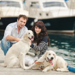 Young couple playing with a dog in the harbor — Stock Photo #48915877