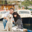 Young couple playing with a dog in the harbor — Stock Photo #48915887