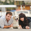 Young couple playing with a dog in the harbor — Stock Photo #48915979